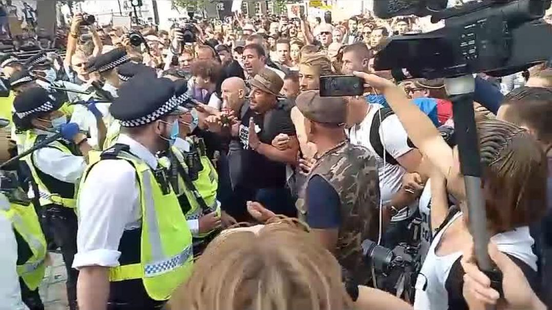 Terrified UK police (in token face masks) surrounded by thousands of angry protestors
